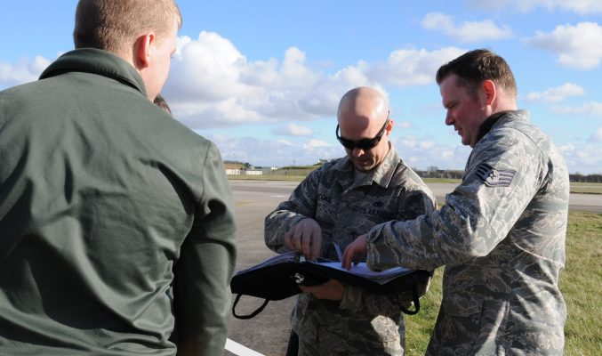 U.S. Air Force Tech. Sgt. Shannon Brooks, center, 100th Aircraft Maintenance Squadron production expeditor from Folio, Calif., reviews an aircraft forms binder which contains aircraft maintenance discrepancies and statuses Feb. 19, 2014, on RAF Mildenhall, England. Brooks improved the wash rack program by establishing a team structure, ensuring the wash teams had transportation and adequate tools, and he implemented a 30-day wash cycle. (U.S. Air Force photo by Gina Randall/Released)